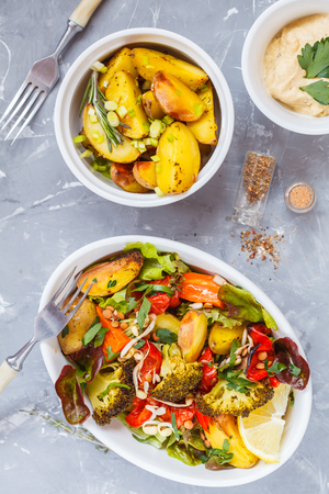 Salad with baked vegetables and hummus, top view. Healthy detox food concept.