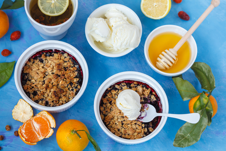 Winter breakfast with berry crumble and tea with lemon. Blue background.