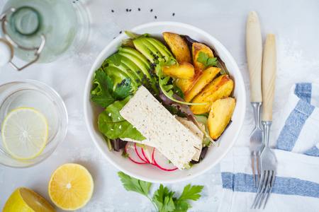 Buddha bowl of salad with tofu, baked potatoes, avocado. Vegan Healthy Food Concept.