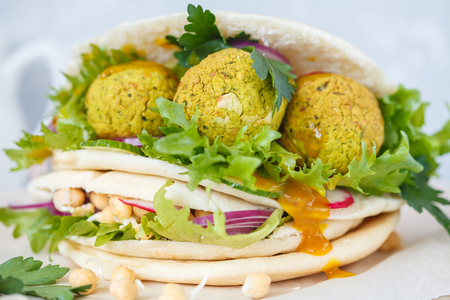 Fresh baked falafel in pita with vegetables, sprouts chickpeas and curry sauce. Vegan Healthy Food Concept.
