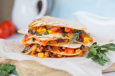 Vegetarian quesadilla with vegetables and cheese on a wooden board, light background. Vegan Healthy Food Concept. Archivio Fotografico
