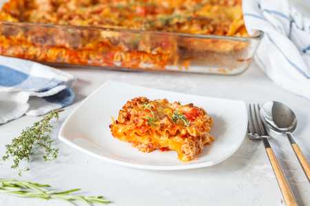 Traditional Italian lasagna baked with herbs and a piece of lasagna on a white plate.