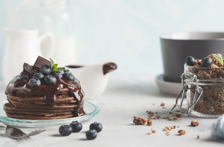 Chocolate pancakes with syrup and berries, chocolate granola, milk and eggs. Breakfast concept
