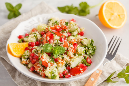 Tabbouleh salad with tomato, cucumber, couscous, mint and pomegranate.  Traditional middle eastern or arab dish. Stock Photo
