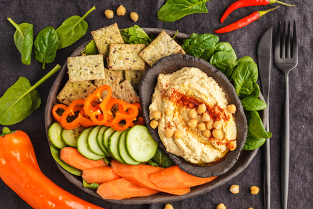 Homemade traditional hummus with vegetables, crackers on a black clay dish, dark background, top view.