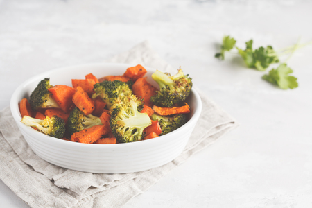Baked broccoli and sweet potato with spices in a white dish. Vegan Healthy Food Concept. Zdjęcie Seryjne