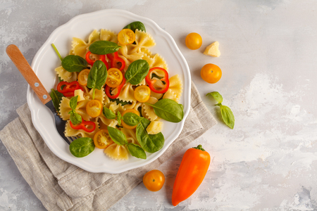 Italian pasta farfalle salad with vegetables, basil and spinach in a white plate. Light background Stock Photo