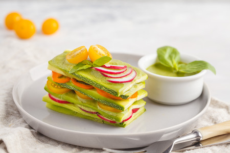 Raw zucchini lasagna with vegetables and pesto sauce, light background. Vegetarian raw diet concept. Stock Photo