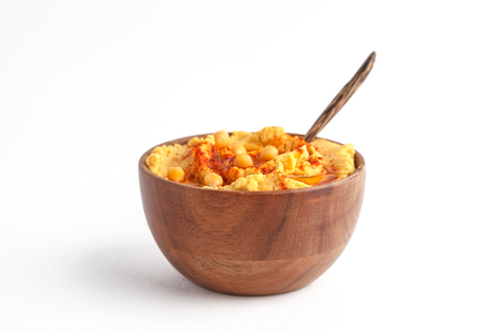 Traditional hummus with paprika in a wooden bowl, isolated on a white background Banque d'images