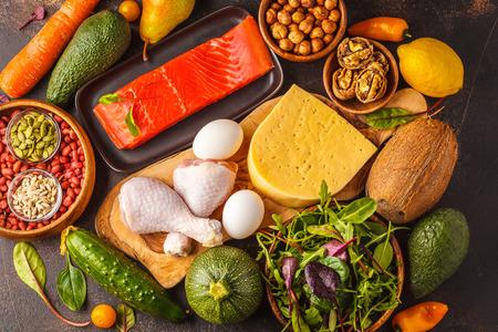 Concept de régime céto. Fond alimentaire équilibré à faible teneur en glucides. Légumes, poisson, viande, fromage, noix sur un fond sombre.