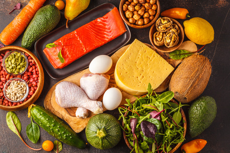 Keto diet concept. Balanced low-carb food background. Vegetables, fish, meat, cheese, nuts on a dark background. Stock Photo
