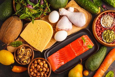 ケトダイエットの概念。バランスのとれた低炭水化物食品の背景。野菜、魚、肉、チーズ、暗い背景にナッツ。 写真素材