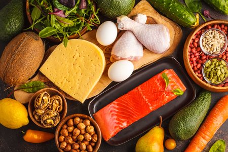 Keto diet concept. Balanced low-carb food background. Vegetables, fish, meat, cheese, nuts on a dark background. Stockfoto