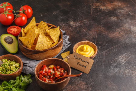 Mexican food concept. Nachos - corn totopos chips with various sauces in wooden bowls: guacamole, cheese sauce, pico del gallo