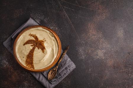 Vegan banana smoothie bowl with a palm tree carob decoration. Vegan healthy food concept