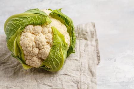 Ripe whole raw cauliflower on a light background on a napkin.