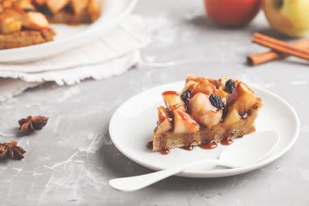 Piece of vegan apple pie with cinnamon, raisins and caramel, gray background.