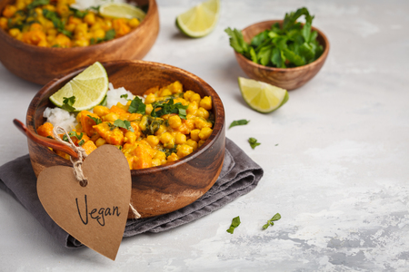 Vegan Sweet Potato Chickpea curry in wooden bowl on a light background. Healthy vegetarian food concept.