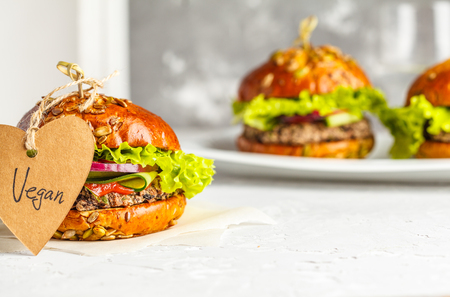 Vegan bean burgers with vegetables and tomato sauce on white dish, copy space. Healthy vegan food concept. Banque d'images