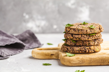 Vegan beans burgers (cutlets) with parsley on a wooden board.  Healthy vegan food concept.