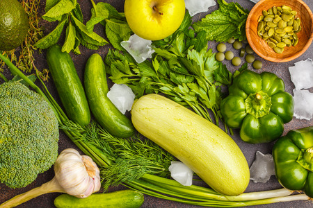 Green vegetables on a dark background. Vegetable vegan diet food background: zucchini, peppers, broccoli, cucumbers, avocado, apple, herbs. Healthy lifestyle concept.