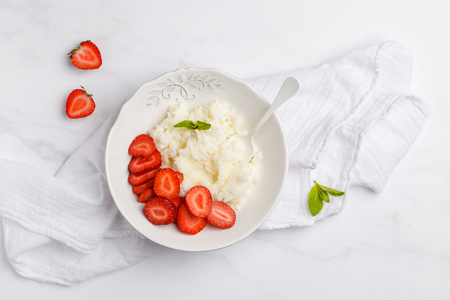 Rice milk porridge with strawberry for breakfast. White background, top view, copy space.