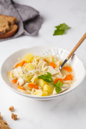 Chicken soup with noodles and vegetables in a white plate, white background. Stock Photo