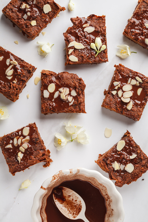 Pieces of pumpkin brownie on white background, top view. Healthy vegan food concept.