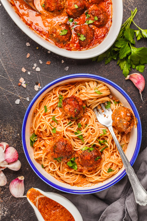 Spaghetti with meatballs in tomato sauce with parsley and garlic in white plate, top view, dark background.