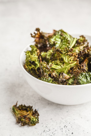 Kale chips in a white bowl on white background. Clean eating concept.