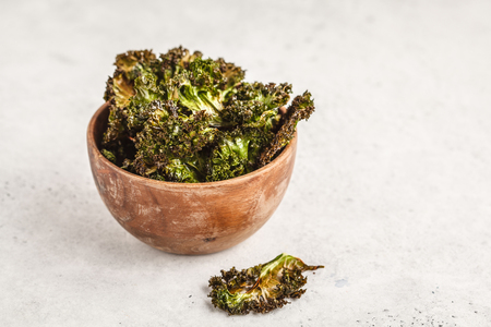 Kale chips in a wooden bowl on white background. Clean eating concept.