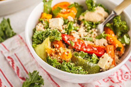 Healthy vegan salad with baked vegetables, quinoa and kale on white background. Clean eating concept.