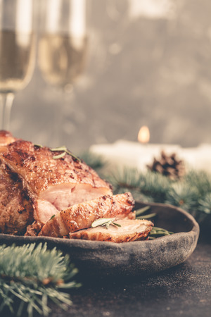 Baked Christmas pork (ham) with rosemary. Christmas table, festive background concept. Spruce twigs all around. Front view. Stock Photo