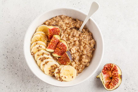 Autumn oatmeal with banana, fig and flax seed. White background, clean eating concept.