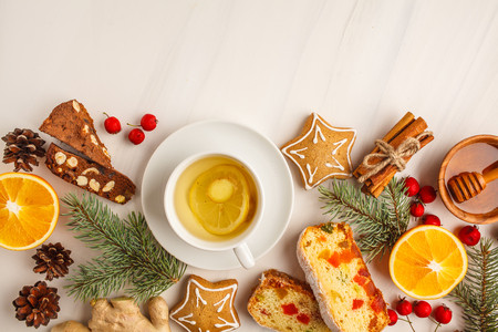 Christmas desserts of different countries (panforte, cookies and Christmas bread) wth tea on a white background, copy space, top view. Stock Photo