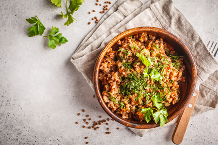 Buckwheat with meat in a wooden bowl on a white background. Russian food, vegan food concept. Stock Photo