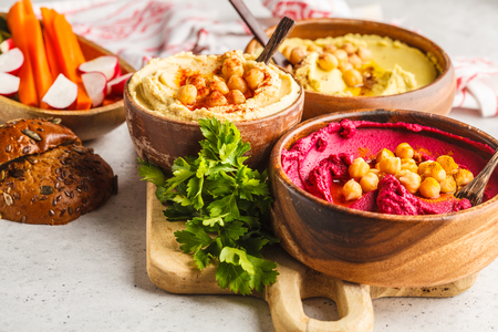 Different hummus bowls. Chickpea hummus, avocado hummus and beet hummus. Plant based diet food.