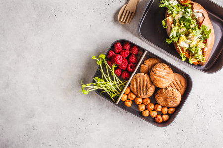 Healthy meal prep containers with quinoa Stuffed Sweet Potatoes, cookies, nuts and berries, overhead shot with copy space. Foto de archivo