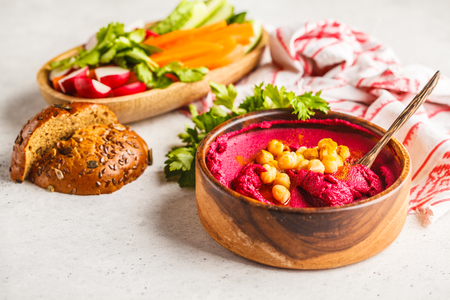 Beet hummus in a wooden bowl with vegetables. Plant based diet concept. Фото со стока
