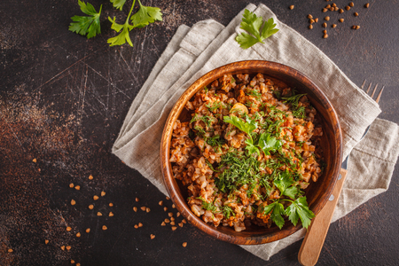 Buckwheat with meat in a wooden bowl on a dark background. Russian food, vegan food concept.