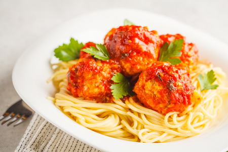 Chicken meatballs with tomato sauce and spaghetti in a white plate, white background.