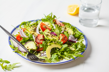 Healthy arugula, avocado, tomatoes salad on white marble background. Plant based diet concept.