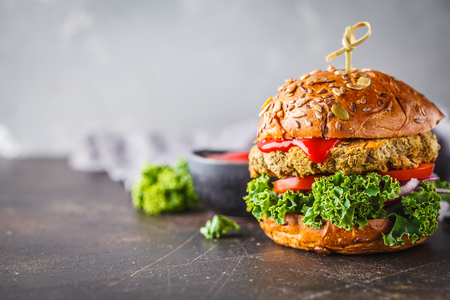 Vegan lentil burgers with kale and tomato sauce on a dark background. Plant based diet cincept.