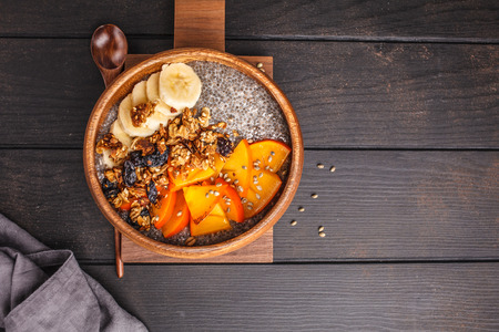 Chia pudding with banana, persimmon and granola, dark wooden background. Healthy vegan food concept.