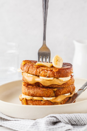 Vegan french toasts with peanut butter, syrup and banana on a white plate.