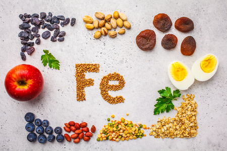 Healthy product sources of Fe. Top view, food background, iron ingredients: buckwheat, dried fruit, apple, eggs on a white background. Stock Photo