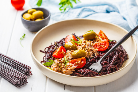 Black rice pasta with tuna, tomatoes and olives in a white plate on white wooden background.