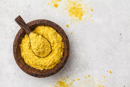 Nutritional yeast in a wooden bowl, copy space, white background, copy space. Healthy vegan food concept. Reklamní fotografie
