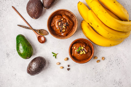 Avocado chocolate mousse with pistachios in a wooden bowl on a white background, top view, copy space.