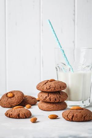 Almond chocolate cookies with milk on a white background. Vegan dessert concept.